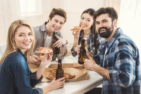 Photo for Two young diverse couples sitting on table and drinking beer and eating pizza - Royalty Free Image