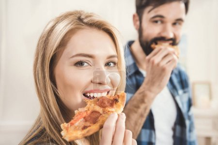 Photo for Young couple eating delicious pizza at home - Royalty Free Image