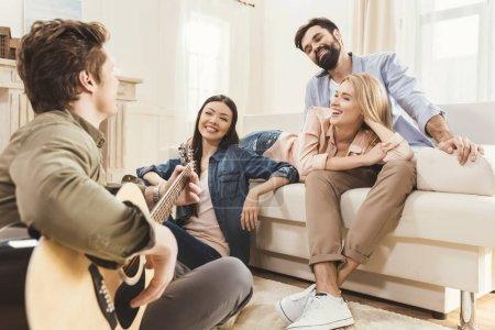 Photo pour Diverses personnes faisant la fête ensemble dans la salle à manger, jouant de la guitare acoustique - image libre de droit