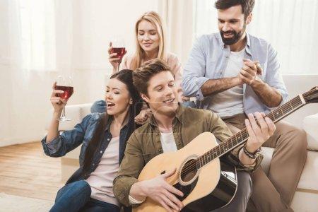Foto de Diversas personas festejando juntos en el comedor, jugando guitarra acústica - Imagen libre de derechos