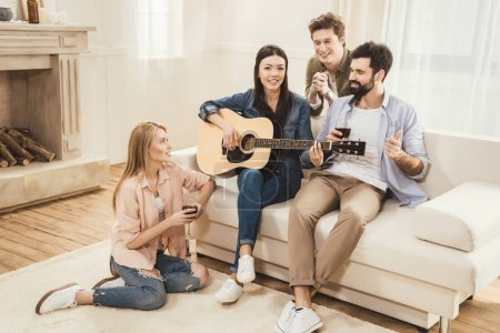 Photo for Diverse people partying together at dining room, playing acoustic guitar - Royalty Free Image