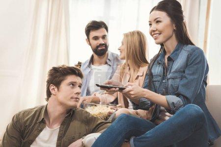 Photo pour Jeunes gens assis sur le canapé avec le pop-corn et de la bière en regardant la télévision - image libre de droit