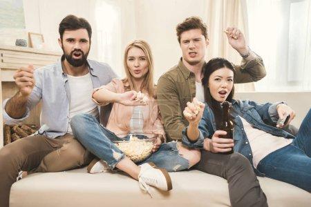 Photo pour Les jeunes gens assis sur le canapé et en jetant des pop-corn à l'envers - image libre de droit