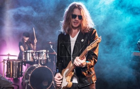 Photo for Electric guitar player with rock and roll band performing hard rock music on stage - Royalty Free Image
