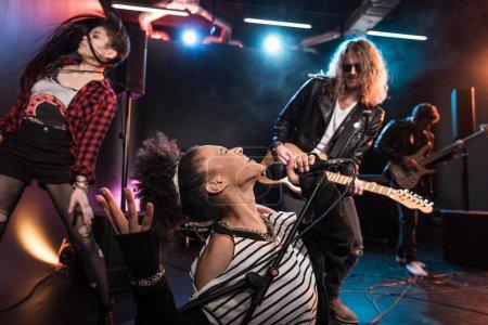 Photo pour Chanteuse avec microphone et groupe de rock and roll jouant de la musique hard rock sur scène - image libre de droit