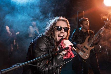 Photo pour Chanteur avec microphone et rock and roll band jouait la musique hard rock sur scène - image libre de droit