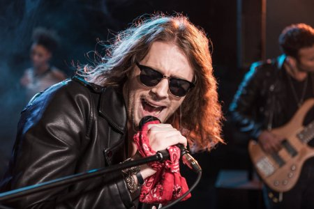 Photo pour Chanteur masculin avec microphone et groupe de rock and roll jouant de la musique hard rock sur scène - image libre de droit