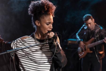 Photo pour Chanteuse avec microphone et rock and roll band jouait la musique hard rock sur scène - image libre de droit