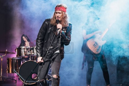Photo for Handsome singer with rock and roll band performing music on stage - Royalty Free Image