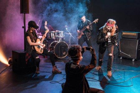 Photo pour Jeune femme assise sur scène et photographiant un groupe de rock and roll - image libre de droit