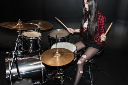 Photo pour La valeur de rock and roll fille jouant de la musique de hard rock avec batterie - image libre de droit