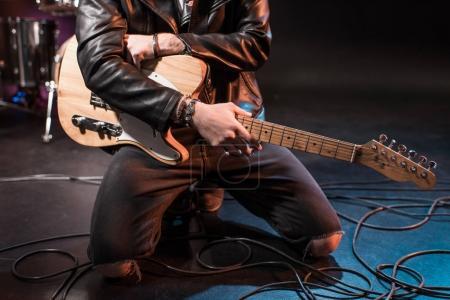 Photo pour Recadrée tir du joueur de guitare électrique à genoux avec guitare basse sur scène - image libre de droit