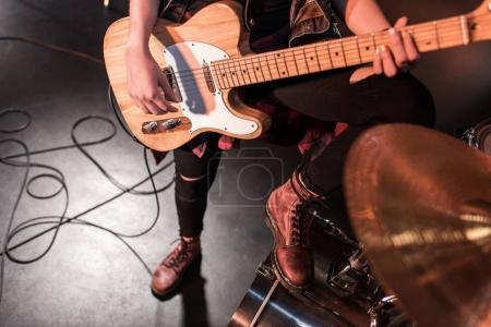 Photo pour Plan recadré de fille rock and roll jouant de la guitare basse sur scène - image libre de droit