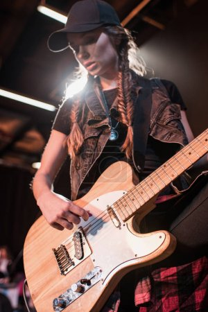 Photo for Young beautiful rock and roll girl playing bass guitar on stage - Royalty Free Image