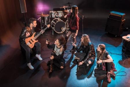 Photo pour Jeune groupe de rock and roll buvant de la bière après un concert sur scène - image libre de droit