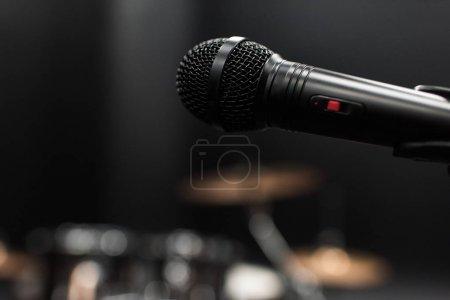 Photo pour Vue rapprochée du microphone électrique noir sur scène vide - image libre de droit