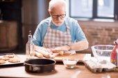 Senior man kneading dough