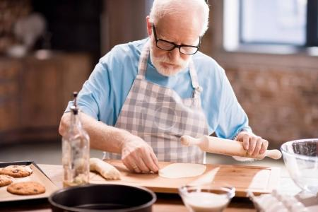 Photo for Senior man cooking and kneading dough for cookies with kitchen utensils at kitchen table, cooking in kitchen concept - Royalty Free Image