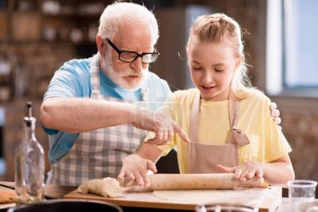 grandfather and granddaughter making dough