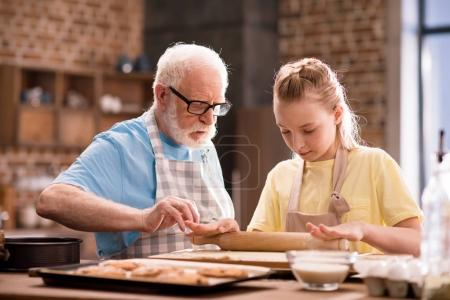 Photo for Grandfather and granddaughter cooking and kneading dough for cookies with kitchen utensils at kitchen table, cooking in kitchen concept - Royalty Free Image