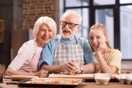 Photo for Grandmother, grandfather and granddaughter cooking and kneading dough for cookies at kitchen table, cooking in kitchen concept - Royalty Free Image