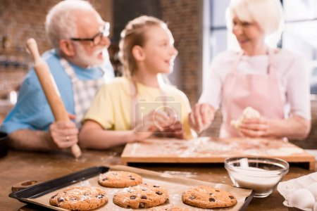 Photo for Grandmother, grandfather and granddaughter cooking and kneading dough for cookies at kitchen table and baked cookies in tray on foreground, cooking in kitchen concept - Royalty Free Image
