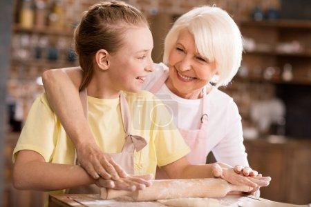 Grandmother and grandchild kneading dough