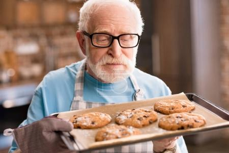 Photo for Senior man in apron holding tray of delicious cookies, cooking in kitchen concept - Royalty Free Image