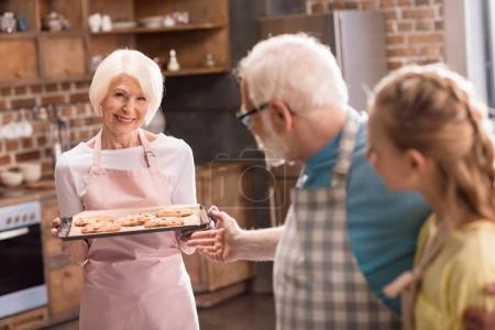 Photo pour Heureux grand-père, grand-mère et petit-enfant regardant plateau avec de délicieux biscuits - image libre de droit