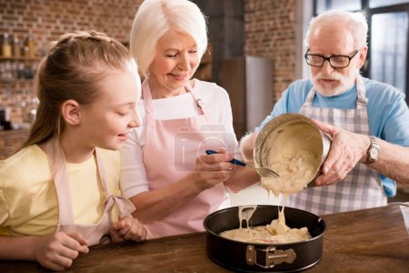 Photo for Happy grandparents and girl cooking together at home - Royalty Free Image