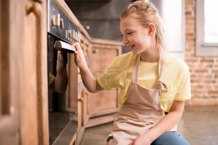 Photo for Side view of smiling little girl near oven in kitchen - Royalty Free Image