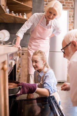 girl placing pie in oven