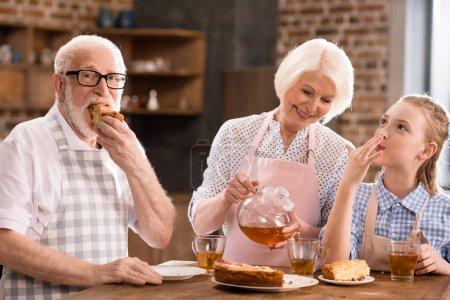 Photo for Grandparents and girl drinking tea with pie together at home - Royalty Free Image