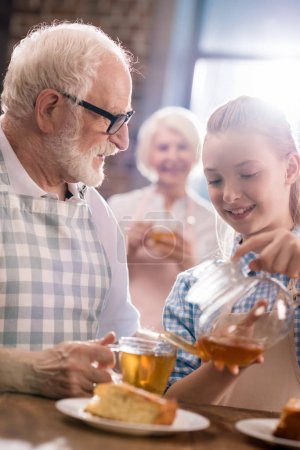 Photo for Portrait of smiling girl pouring tea in grandfather's cup - Royalty Free Image