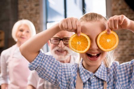 girl holding orange slices