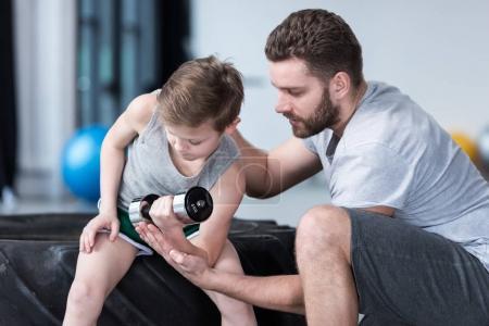 Photo pour Entraînement de garçon avec haltère avec entraîneur au centre de fitness - image libre de droit