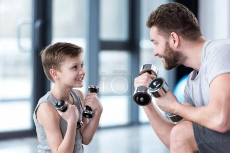 Photo for Boy training with dumbbells together with coach at fitness center - Royalty Free Image