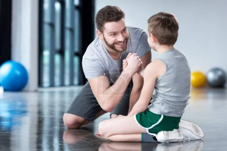 Boy with young man at fitness center