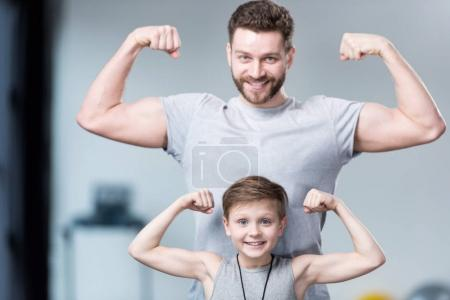 Photo for Boy with young man, his trainer or father showing muscles - Royalty Free Image