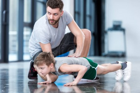 Boy doing push ups with coach