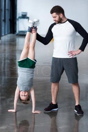 Photo pour Formateur aidant garçon debout sur les mains à la salle d'exercice - image libre de droit