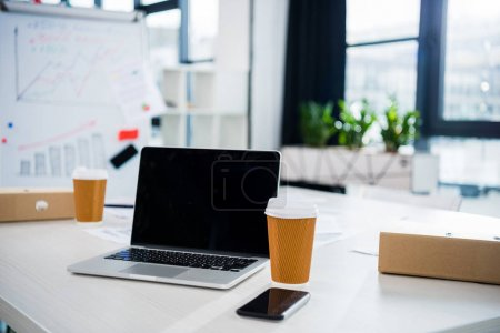 Photo for Laptop computer, smartphone and coffee cups on workplace in empty office, small business office - Royalty Free Image