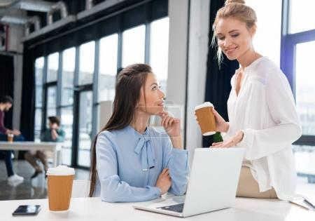 Photo for Smiling young businesswomen using laptop and talking at workplace - Royalty Free Image