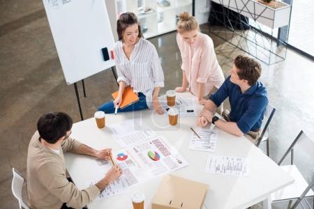 Photo pour Vue d'angle élevé de jeunes gens d'affaires discutant graphiques sur lieu de travail - image libre de droit
