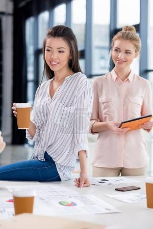 Photo for Young businesswomen with cup of coffee and tablet at modern workplace - Royalty Free Image