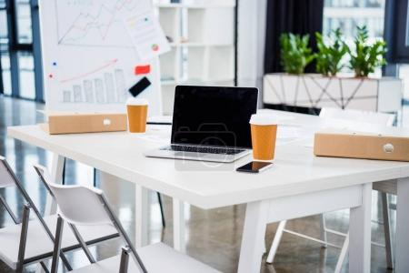 Photo pour Lieu de travail avec ordinateur portable, tasses en papier café dans le bureau moderne - image libre de droit
