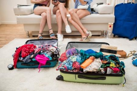 Photo for Young women packing suitcases for vacation together at home, travel bags concept - Royalty Free Image