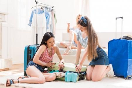 Photo pour Jeunes femmes emballant des valises pour des vacances ensemble à la maison, concept d'emballage de bagages - image libre de droit