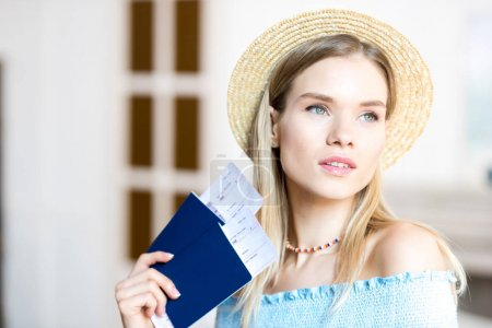 Photo for Portrait of beautiful young blonde woman in hat holding passports and tickets, getting ready to travel concept - Royalty Free Image