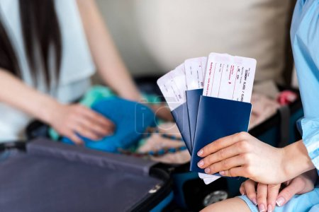 Photo for Close-up partial view of woman holding passports and tickets, getting ready to travel concept - Royalty Free Image